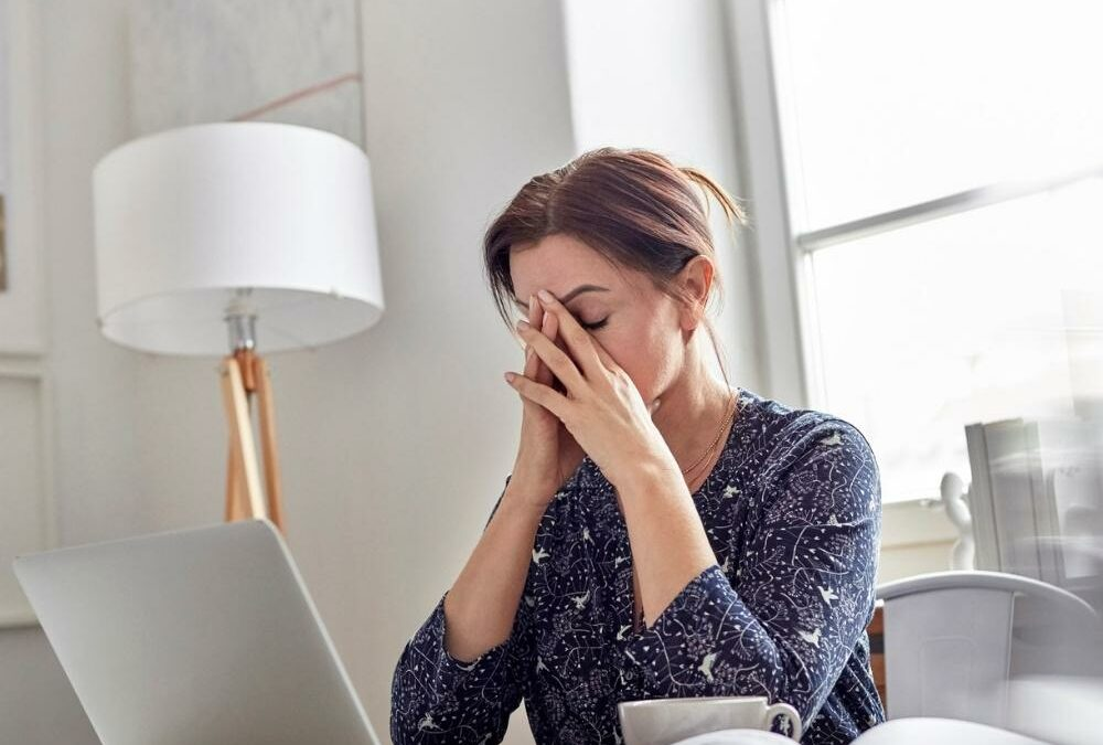 woman hiding her face in her hands while in front of a computer